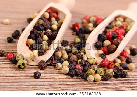 Heap of fresh colored pepper with wooden spoon lying on wooden table, seasoning for cooking, concept for healthy nutrition