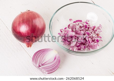 Heap of fresh finely diced red onion with a peeled half showing a cross-section and whole unpeeled one behind on a white background - stock photo