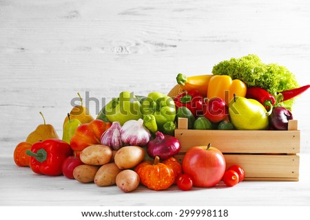 Heap of fresh fruits and vegetables on wooden background - stock photo