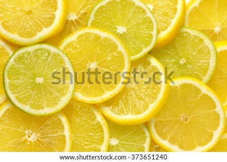 heap of fresh lemon and lime slices - full frame - stock photo