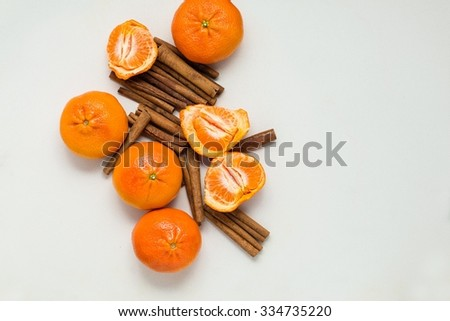 Heap of fresh mandarin fruits and dried cinnamon sticks, top view - stock photo