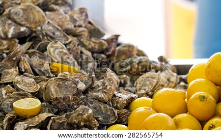 Heap of fresh oysters with lemons in restaurant - stock photo