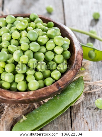 Heap of fresh Peas on wooden background (close-up shot) - stock photo