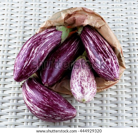 Heap of Fresh Raw Striped Eggplants into Paper Bag closeup on Wicker background - stock photo
