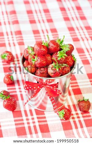 Heap of fresh red ripe strawberry in decorative aluminium bucket. Indoors closeup. - stock photo