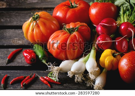 Heap of fresh ripe colorful vegetables tomatoes, chili peppers, green onion and bunch of radish over old wooden table. Dark rustic atmosphere - stock photo