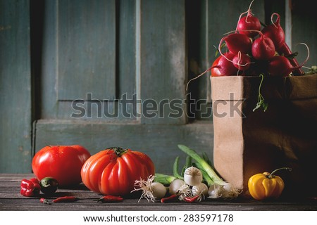 Heap of fresh ripe colorful vegetables tomatoes, chili peppers, green onion and bunch of radish in paper bag over old wooden table. Dark rustic atmosphere - stock photo