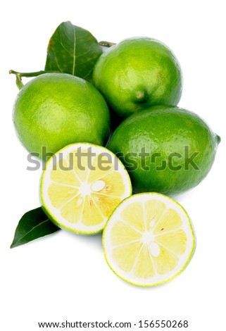 Heap of Fresh Ripe Green Lemons with Halves and Leafs isolated on white background