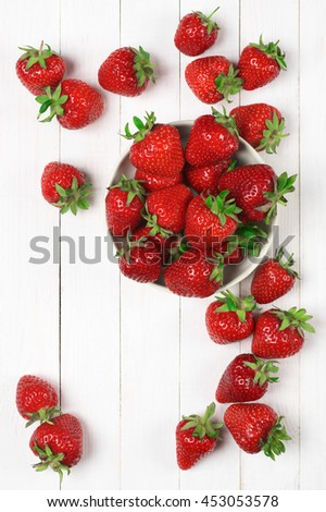 Heap of fresh strawberries in bowl on white wooden background. Top view point.