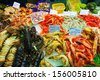 Heap of fresh uncooked seafood on market counter - stock photo