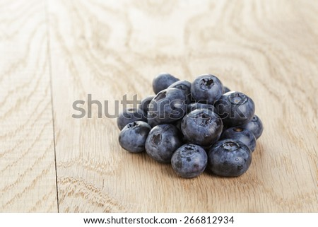 heap of fresh washed blueberries on wooden table