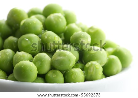 Heap of fresh wet green peas in white dish on white background. - stock photo