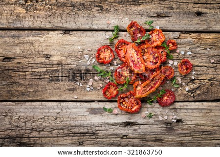 Heap of freshly dried tomatoes on wooden background - stock photo