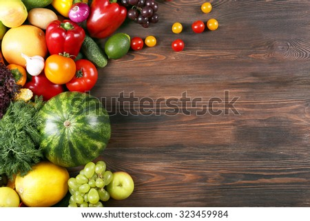 Heap of fruits and vegetables on wooden background - stock photo
