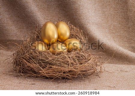 Heap of golden easter egg in nest on sack background - stock photo