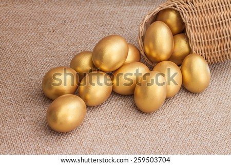 Heap of golden easter egg in wicker basket on brown sack background - stock photo