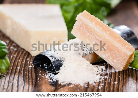 Heap of grated Parmesan (close-up shot) on wooden background - stock photo