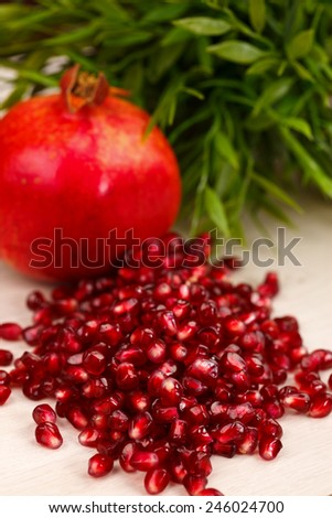 Heap of grenadine seeds with fruit and green leaves in the back - stock photo