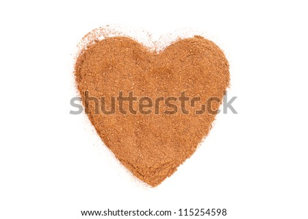 Heap of ground Cinnamon isolated in heart shape on white background.  As a spice or condiment cinnamon sold in the form of sticks or a hammer. Used as a spice in cuisines all over the world.