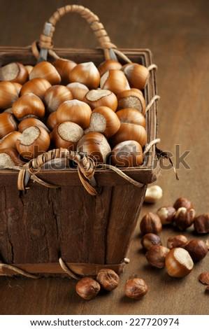 Heap of hazelnuts in basket on wood. - stock photo