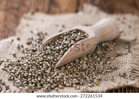 Heap of Hemp Seeds on wooden background (close shot) - stock photo