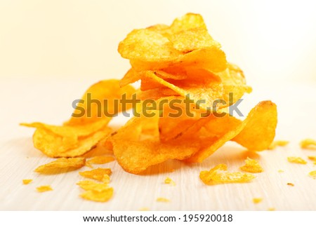 Heap of homemade potato chips on light background - stock photo