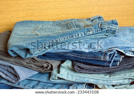 Heap of indigo jeans on sale. Front view close-up - stock photo