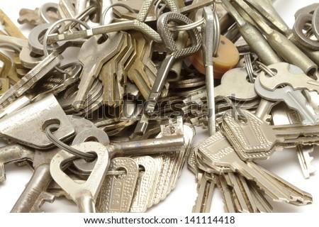 Heap of keys on white - stock photo