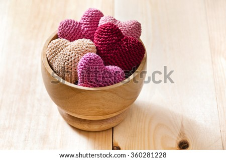 Heap of knitted hearts in a wooden bowl on a wooden table. Background Valentines Day.Valentines day cards. - stock photo