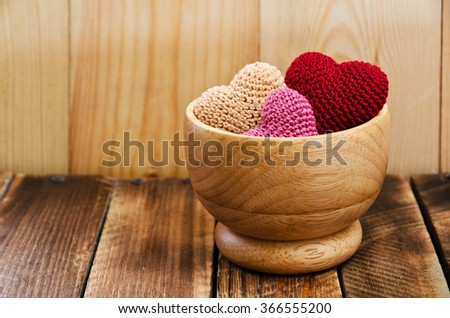 Heap of knitted hearts in a wooden bowl on a wooden table. Background Valentines Day.Valentines day cards.