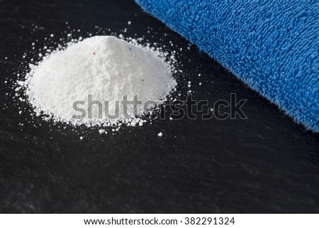 Heap of laundry detergent with blue towel - stock photo