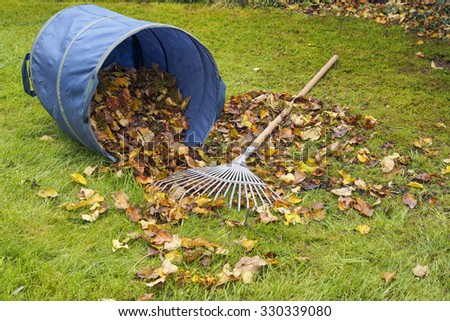 Heap of leaves, rake and fallen dirt bag on green garden lawn, garden works and cleaning in autumn. - stock photo