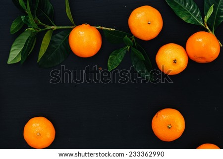 Heap of mandarins on a black background - stock photo