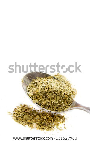 Heap of mate tea with spoon close up isolated on white background.