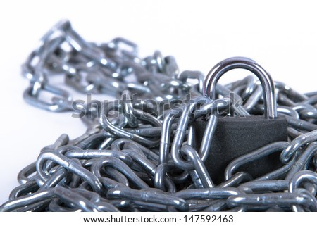 Heap of metal chain with security lock, isolated on white background.