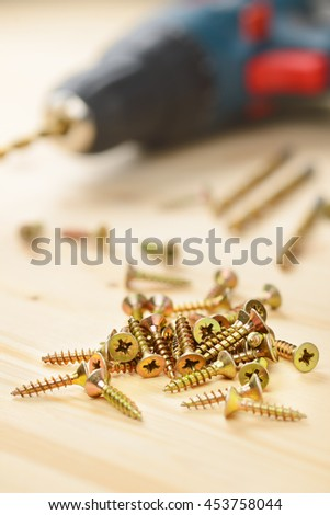 Heap of metal screws and electric drill in wooden board - stock photo