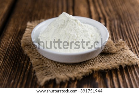 Heap of Milk Powder (selective focus) on an old wooden table - stock photo