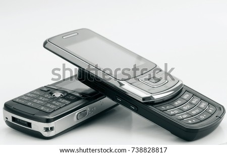 Heap of mobile phones on light background. Shallow depth of field.