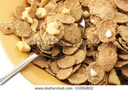 Heap of muesli in orange plate with spoon close-up on white background.