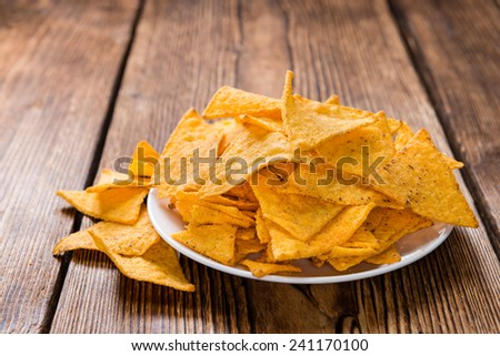 Heap of Nachos on rustic wooden background (close-up shot) - stock photo