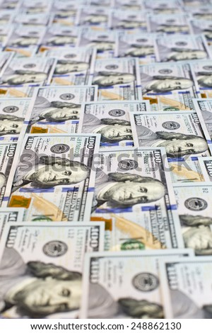 Heap of new US cash in hundred notes. Heap of US dollars in hundred notes covering the table - stock photo