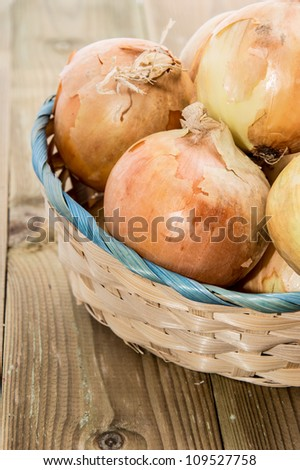 Heap of Onions in a basket on wooden background