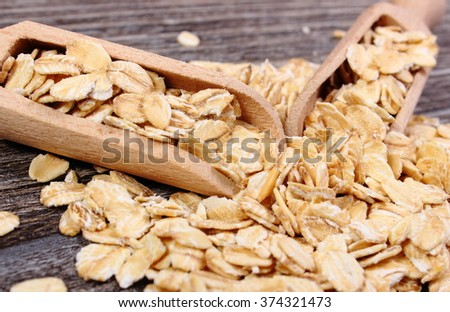 Heap of organic oatmeal, oat flakes with wooden spoon on wooden background, concept for healthy eating and nutrition