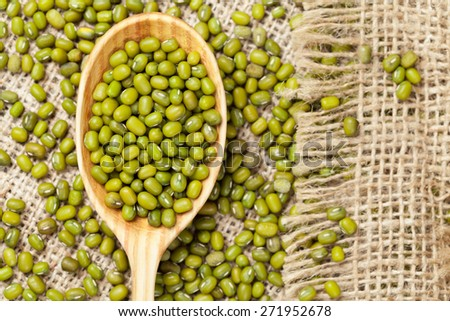 Heap of organic raw green mung bean lentils in wooden spoon on vintage textile background - stock photo