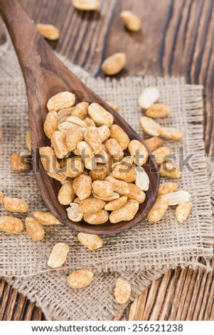 Heap of Peanuts (roasted and salted) on dark wooden background - stock photo