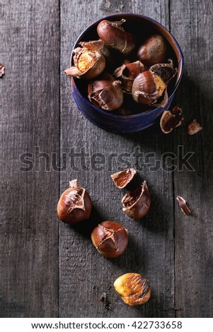 Heap of peeled  and unpeeled grilled edible chestnuts in tin purple jar over old wooden surface. Top view - stock photo