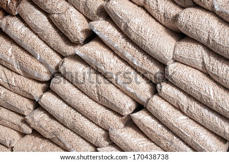 Heap of Pine pellets infront apile of fire wood - stock photo