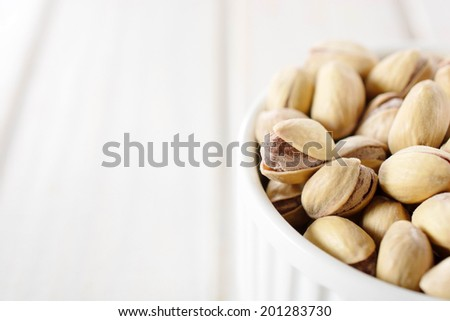 Heap of pistachio in the cup and blank space on left side for text.Selective focus on pistachio on the left - stock photo