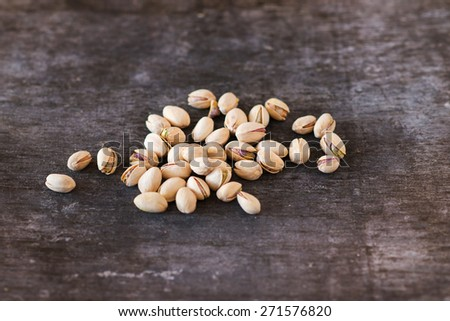 Heap of pistachio nuts, close up on wooden table background - stock photo