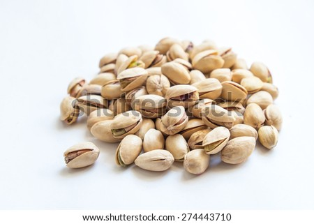 Heap of pistachios nuts in isolated white background. Nuts in shell, cleaned and peeled. Clipping path included. - stock photo